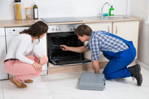 Woman Looking At Male Worker Repairing Oven Appliance In Kitchen Room