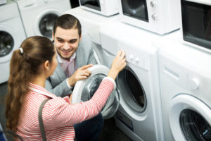 Happy family couple buying new clothes washer
